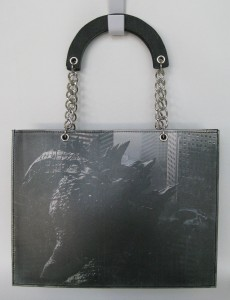 The front and back of this bag are the same image with a matt plastic coating; magnetic snap closure inside the bag.